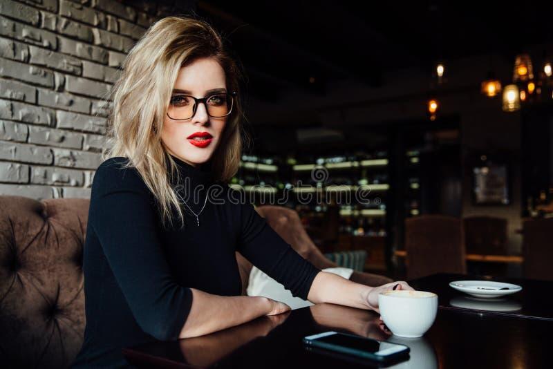 Jonge het glimlachen bedrijfsvrouwenzitting in koffie bij lijst, leunende hand op lijst en het houden van smartphone royalty-vrije stock fotografie
