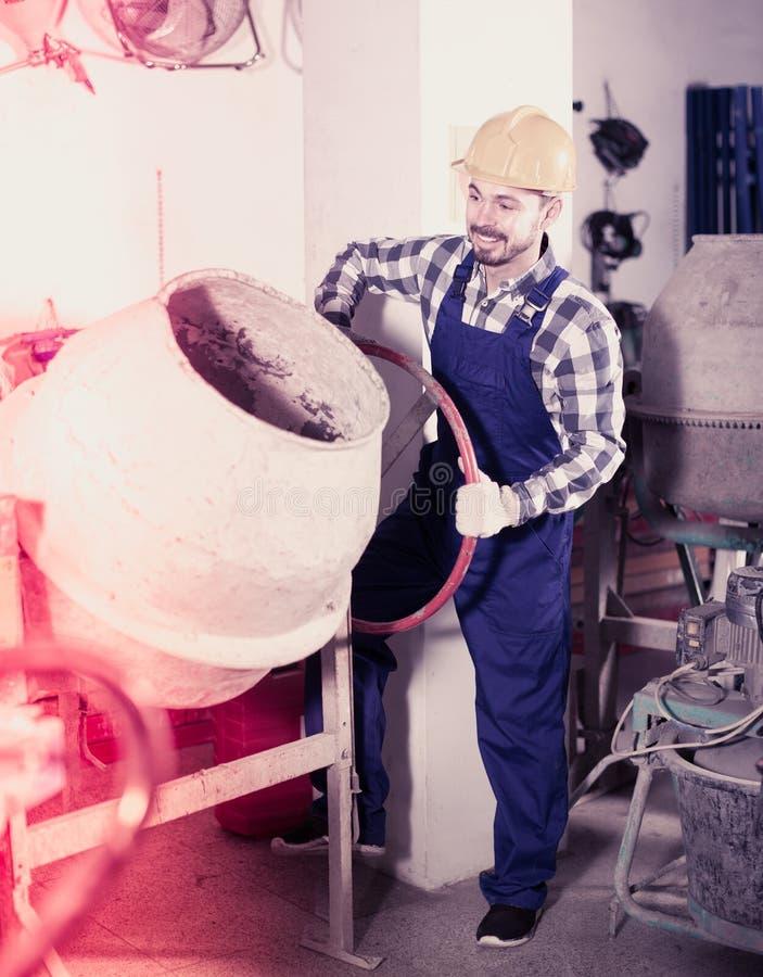 Jonge het glimlachen kerel die concrete mixer met behulp van op workshop royalty-vrije stock foto's