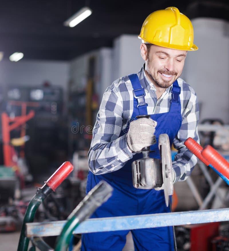 Jonge het glimlachen kerel die hoekmolen voor bouw met behulp van stock foto's