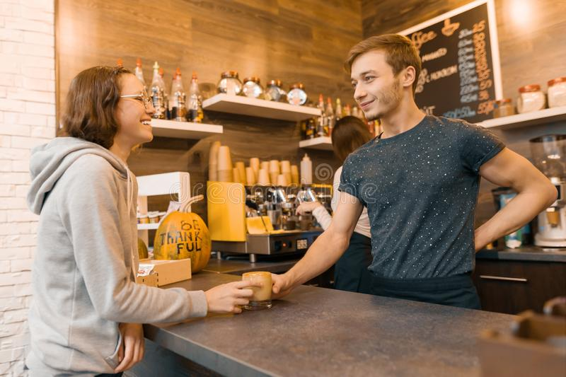 Jonge het glimlachen mannelijke barista verkopende drank aan een tienermeisje in koffiewinkel royalty-vrije stock foto