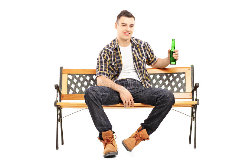 Jonge het glimlachen mensenzitting op een bank en holding een bierfles royalty-vrije stock fotografie