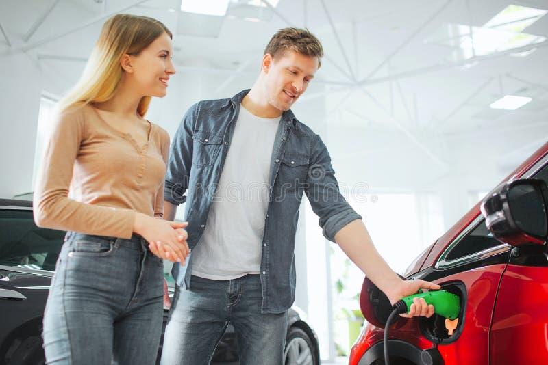 Jonge het glimlachen paar het kopen eerste elektrische auto in de toonzaal Mens die modern milieuvriendelijk voertuig belasten me royalty-vrije stock foto