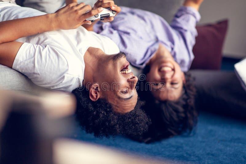 Jonge het glimlachen paar het spelen videospelletjes thuis royalty-vrije stock afbeelding