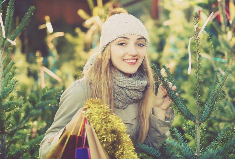 Jonge het glimlachen vrouw het kopen Kerstmisboom bij feestelijke markt stock foto's