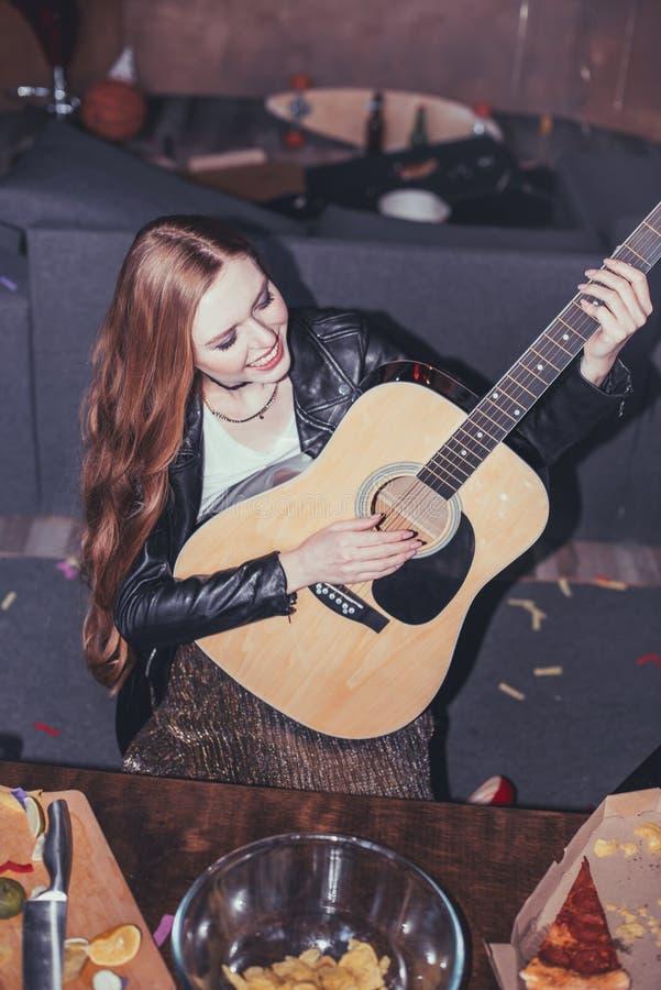 Jonge het glimlachen vrouw het spelen gitaar bij partij royalty-vrije stock foto