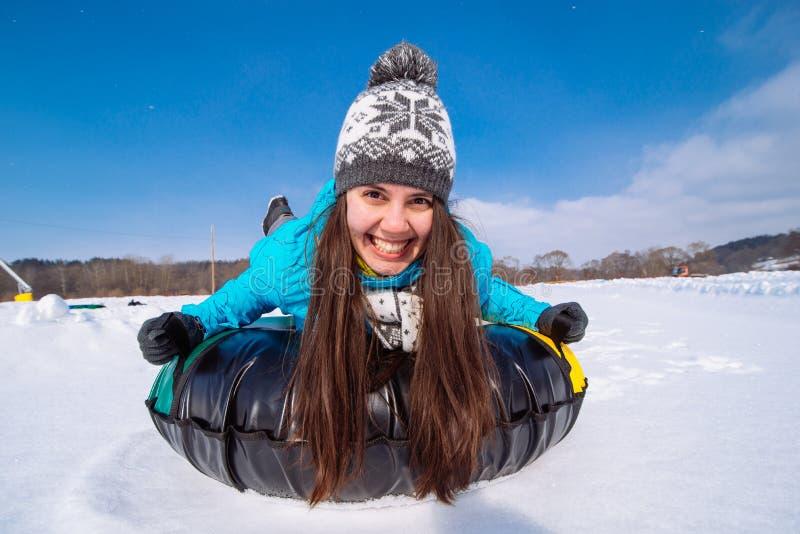 Jonge het glimlachen vrouwengreep voor ar Sneeuwbuizenstelsel De winteractiviteit stock afbeelding