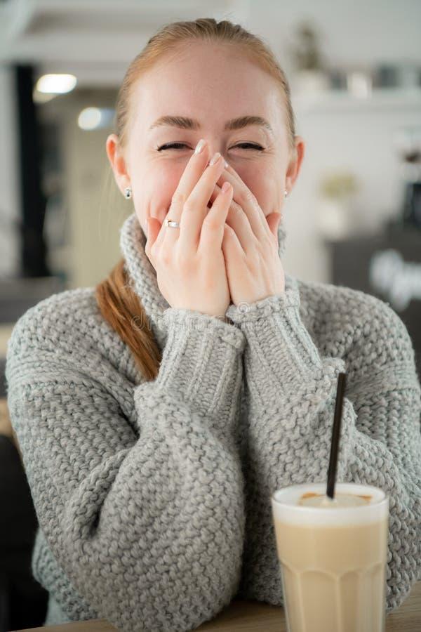 Jonge het glimlachen vrouwenzitting in koffie bij lijst die met handen op haar mond glimlachen Hipstergember, geeuwen, die zijn m royalty-vrije stock afbeeldingen