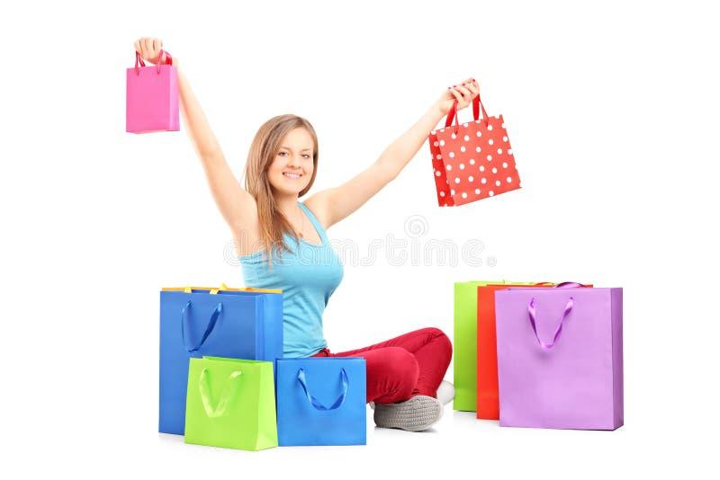 Jonge het glimlachen vrouwenzitting op een vloer en holdings het winkelen zakken stock foto