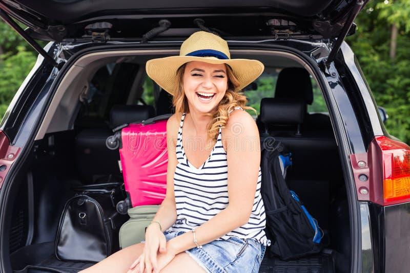 Jonge het lachen vrouwenzitting in de open boomstam van een auto De Reis van de de zomerweg stock fotografie