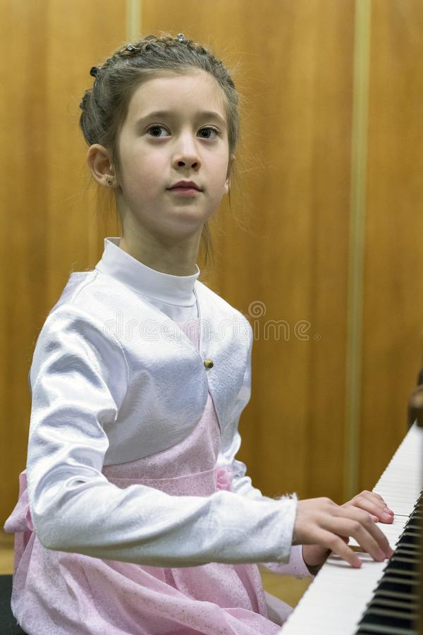 Jonge het Spelen van het Meisje Piano Een meisje in een mooie kledingsspelen op een bruine grote piano Verticale foto royalty-vrije stock afbeeldingen