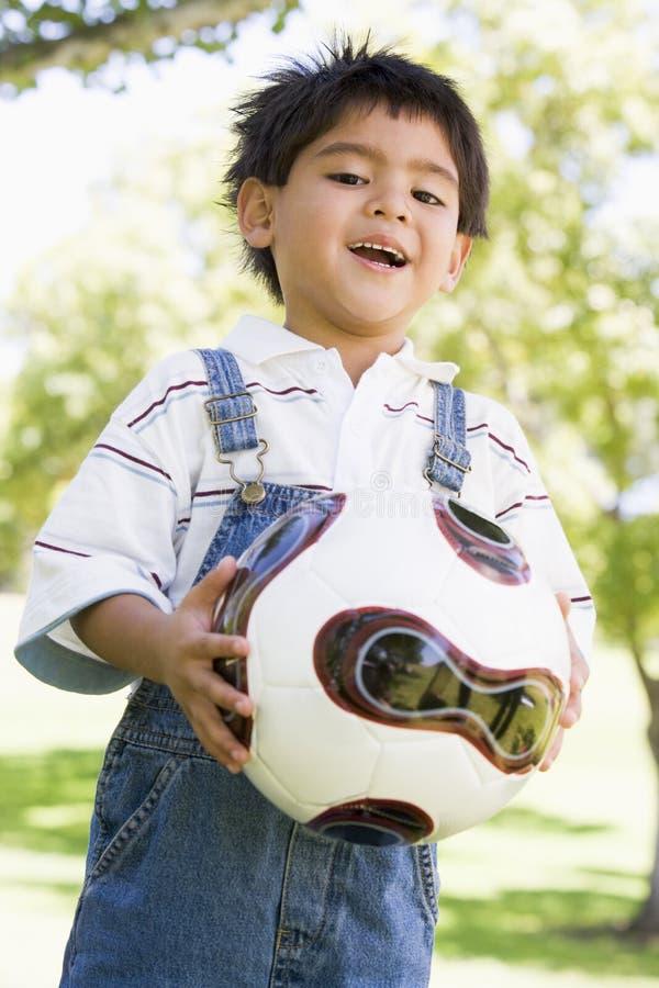 Jonge het voetbalbal die van de jongensholding in openlucht glimlacht royalty-vrije stock afbeeldingen