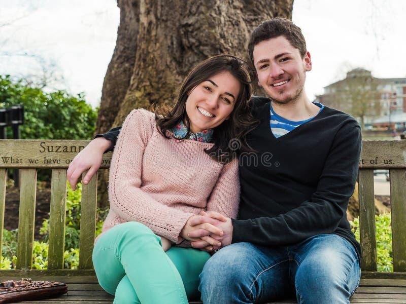 Jonge Heteroseksuele Paarzitting op een Parkbank royalty-vrije stock foto's