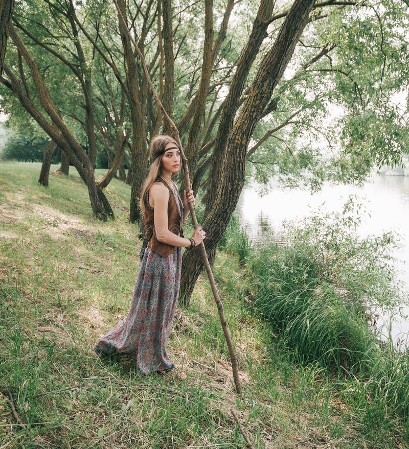 Jonge hippievrouw die zich dichtbij bosmeer bevinden stock afbeeldingen