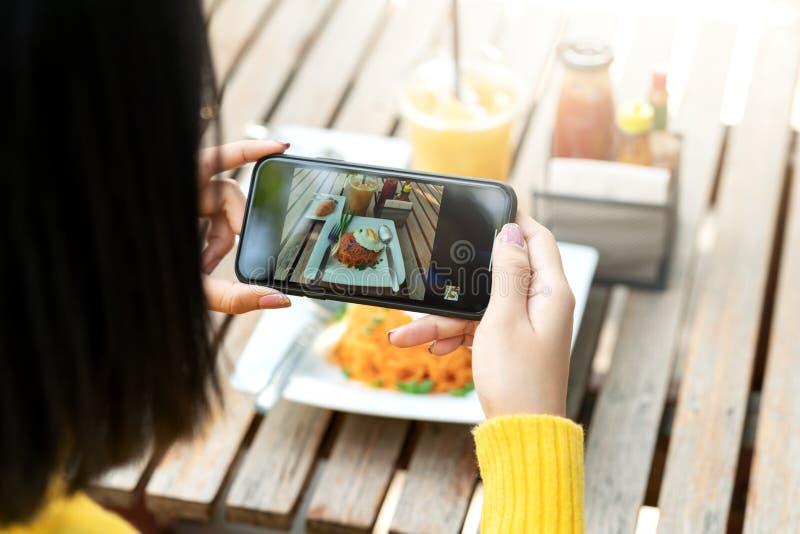 Jonge hipster Aziatische blogger neemt foto van voedsel, plaat, gezond recept, lunchmaaltijd, ontbijtaandeel aan verhaalinhoud in royalty-vrije stock fotografie