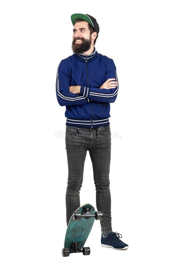Jonge hipster in blauw bovenkledijjasje en honkbal GLB op skateboard die weg glimlachend kijken stock foto's