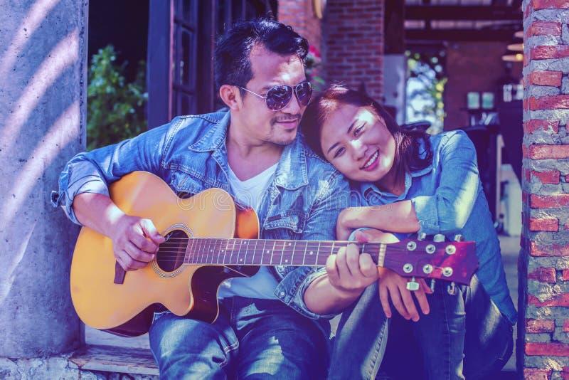 Jonge hipster oefende gitaar in het gelukkige park uit, en geniet van speel gitaar royalty-vrije stock foto