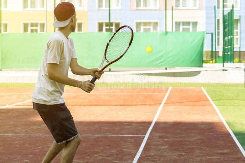 Jonge hipster op het hof de toevallige tennisspeler stock fotografie