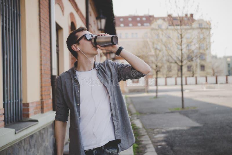 Jonge hipstermens die op de de straat en het drinken koffie lopen royalty-vrije stock foto