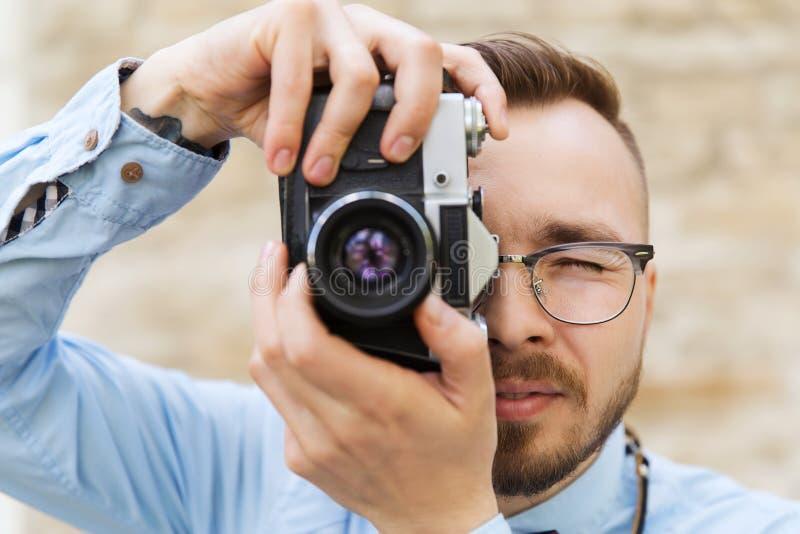 Jonge hipstermens met filmcamera in stad stock afbeelding