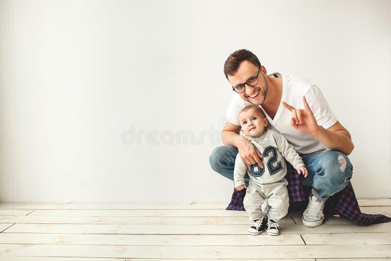 Jonge hipstervader en babyjongen op houten vloer royalty-vrije stock fotografie