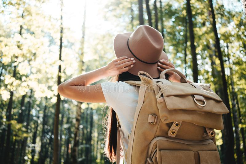 Jonge hipstervrouw die alleen in openlucht onder bomen en greephoed zijn handen reizen Knap meisje die reizigersrugzak dragen stock foto