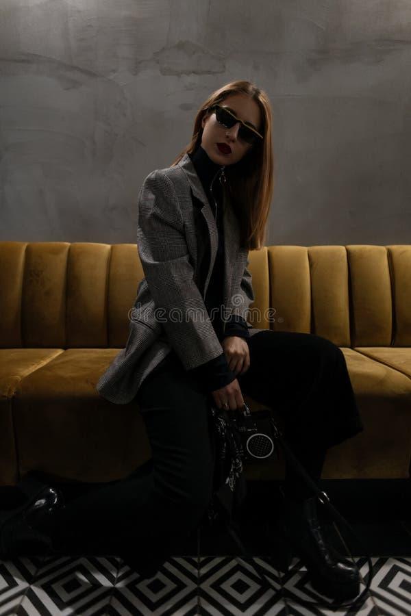 Jonge hipstervrouw in zonnebril met een doordrongen neus in een geruit jasje in retro stijl met een modieus handtas-registreertoe stock foto's