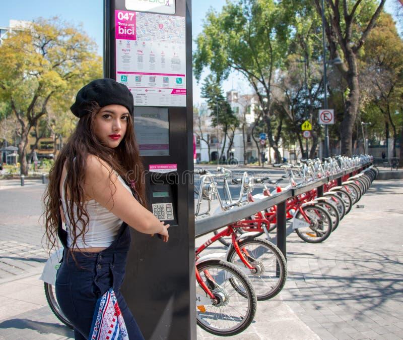 Jonge hispterdame die de straatfietsen van het Mexicaanse stedelijke programma EcoBici met behulp van royalty-vrije stock afbeeldingen