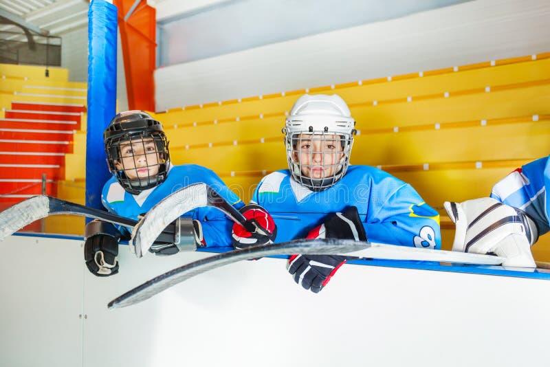 Jonge hockeyspelers die op bank bij stadion zitten royalty-vrije stock fotografie
