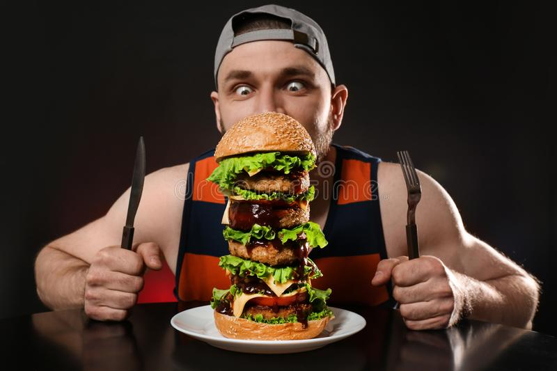 Jonge hongerige mens die met bestek reusachtige hamburger op zwarte eten stock afbeeldingen