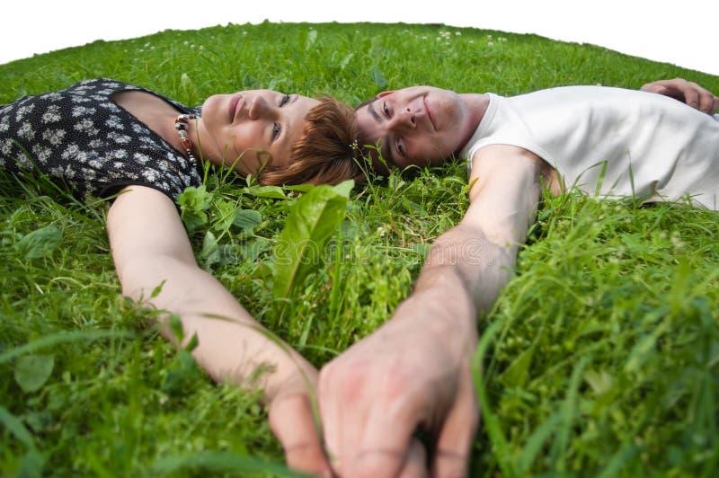 Jonge houdende van paartieners die op groene gras leggen stock afbeelding