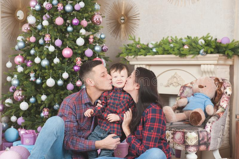 Jonge huiselijke man en vrouw die klein jong geitje in vrolijke Kerstmis kussen stock foto