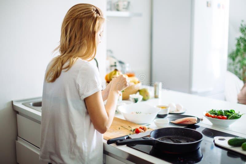 Jonge huisvrouw die maaltijd voor linch in keuken maken Achter mening royalty-vrije stock foto's