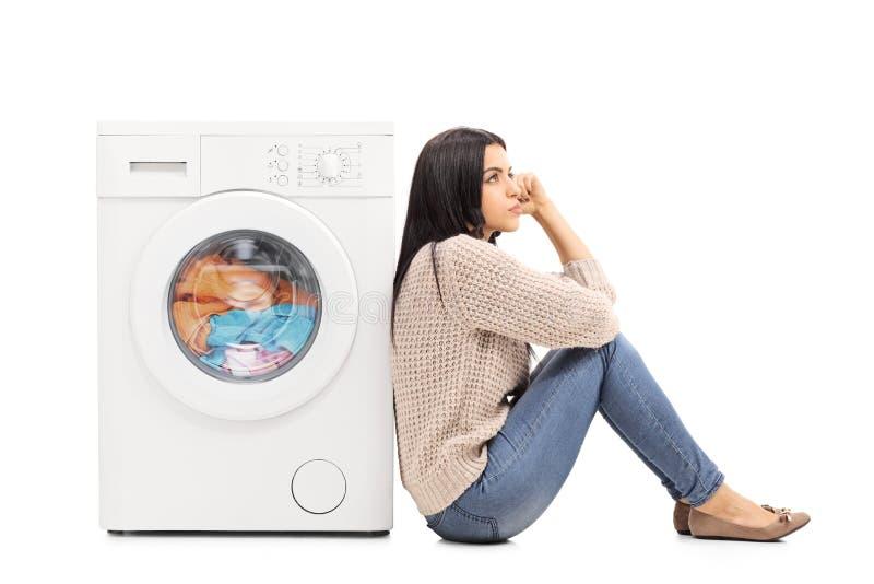 Jonge huisvrouw die op de wasserij wachten stock foto's