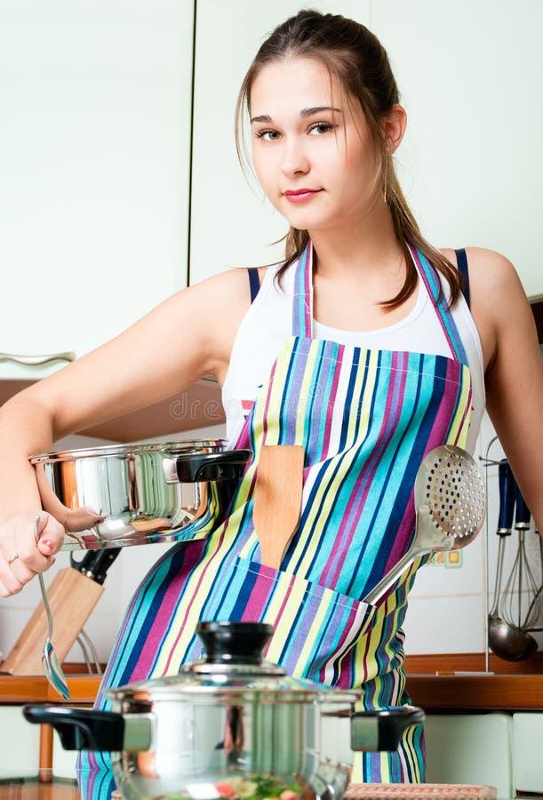 Jonge huisvrouw op binnenlandse keuken stock afbeelding