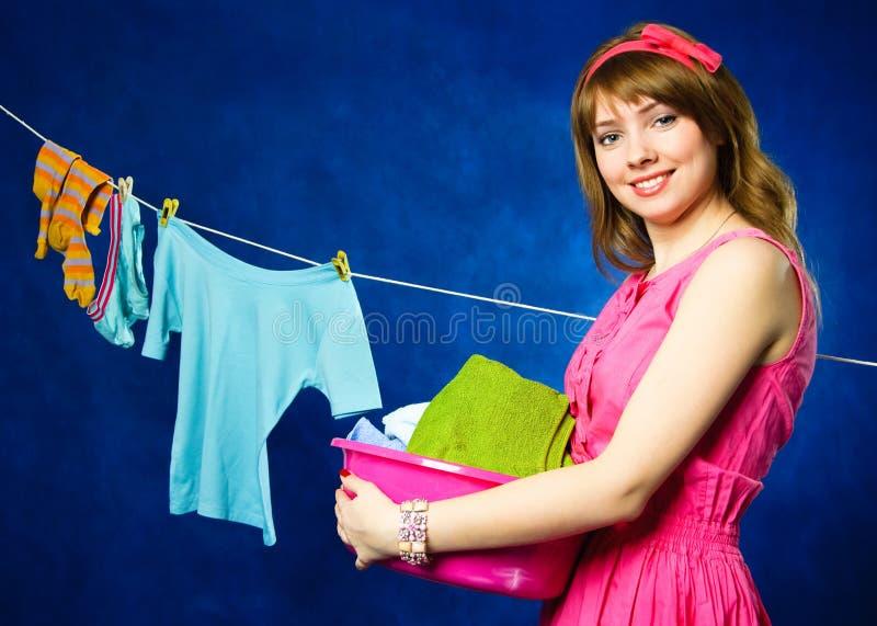 Jonge huisvrouwen hangende kleren op drooglijn royalty-vrije stock afbeeldingen