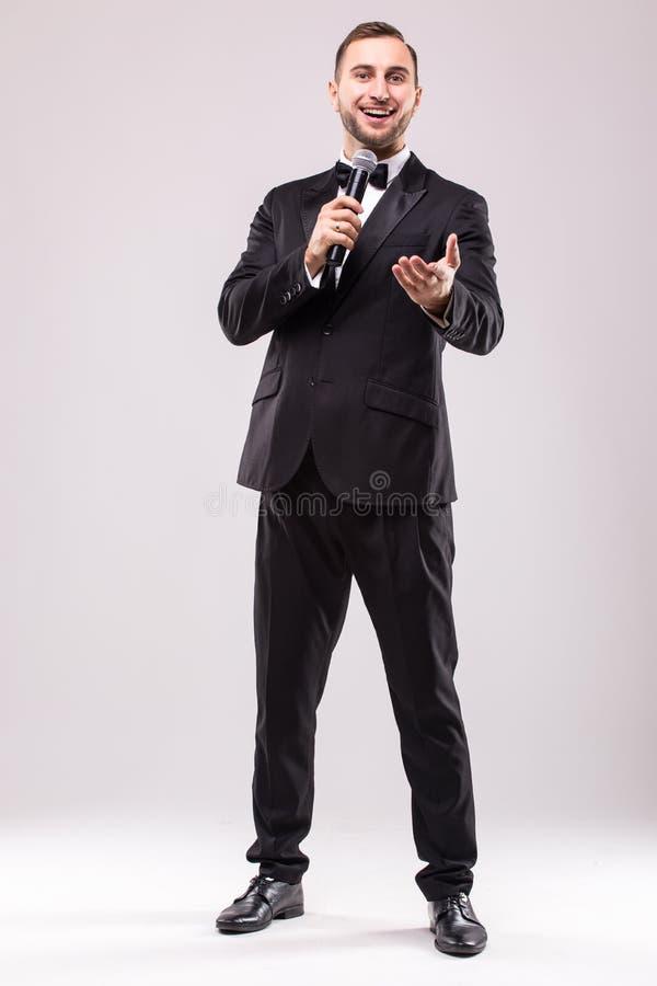 Jonge Impresariopresentator met microfoon tegen witte achtergrond royalty-vrije stock afbeelding