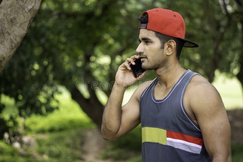 Jonge Indische atletenmens die smartphone na jogging in park gebruiken royalty-vrije stock foto