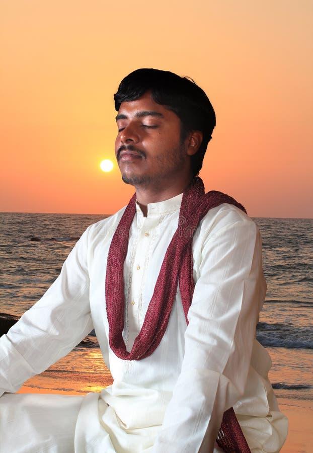 Jonge Indische mens in meditatiehouding bij strand royalty-vrije stock foto's