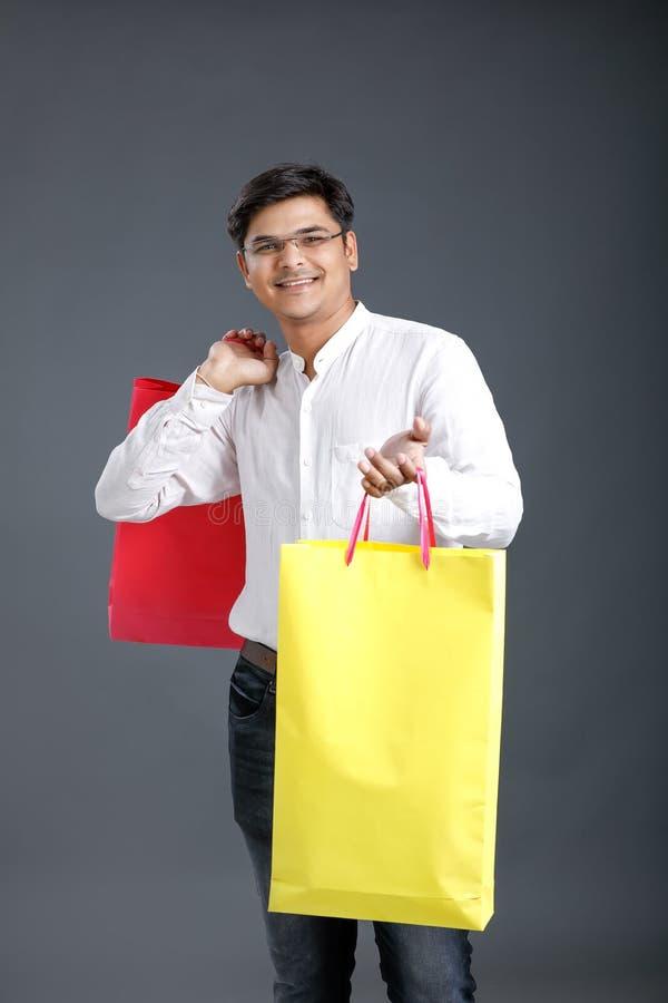 Jonge Indische mens met het winkelen zakken stock afbeeldingen