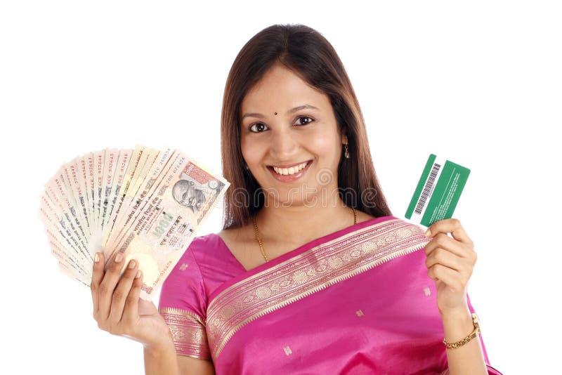 Jonge Indische vrouw die Indische munt & creditcard houden stock fotografie