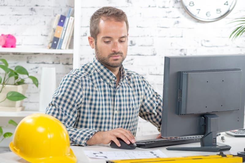 Jonge ingenieur die aan zijn computer werken stock foto's