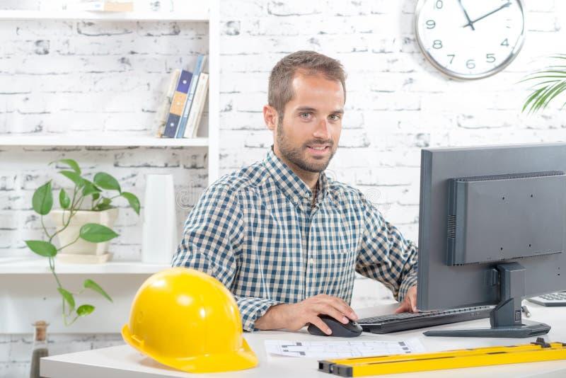 Jonge ingenieur die aan zijn computer werken stock foto