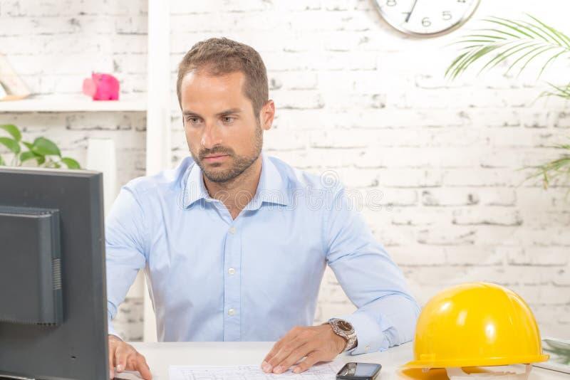 Jonge ingenieur die aan zijn computer werken stock afbeeldingen