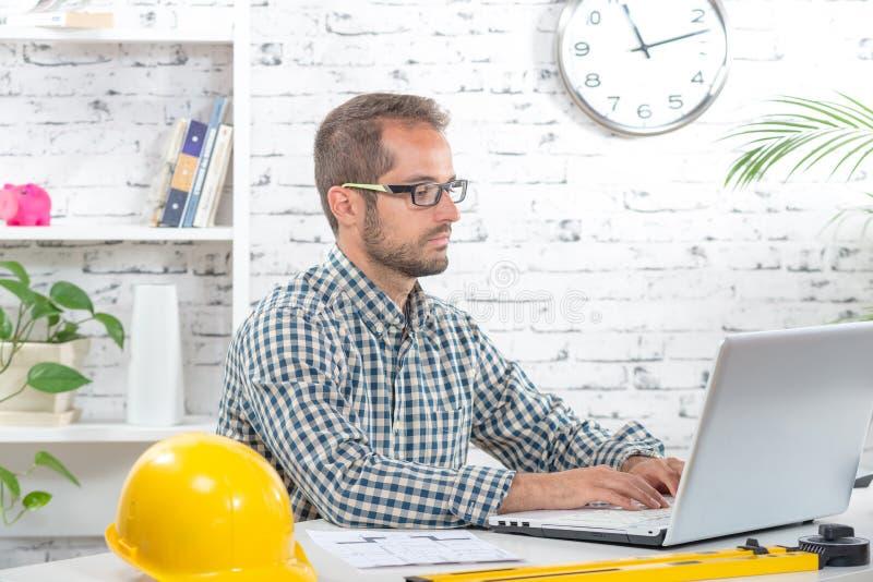 Jonge ingenieur die aan zijn laptop werken stock foto's
