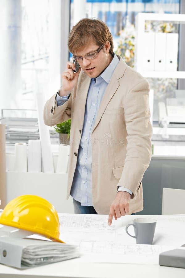 Jonge ingenieur die op telefoon spreken die op plan richten stock foto