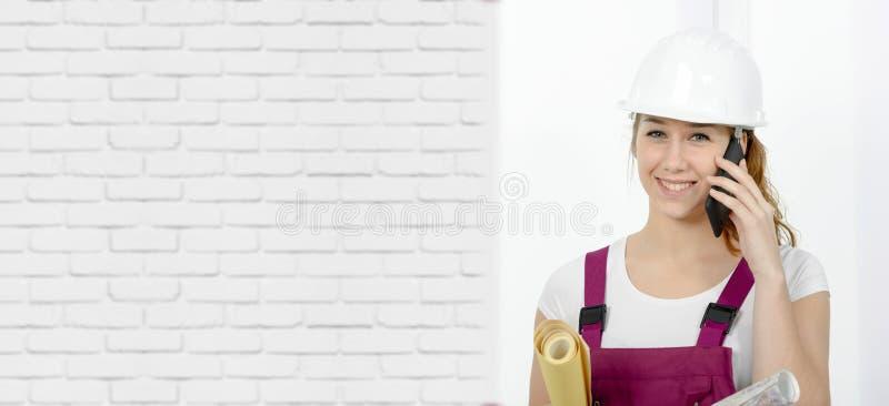 Jonge ingenieursvrouw die met veiligheidsbouwvakker op telefoon spreken stock foto
