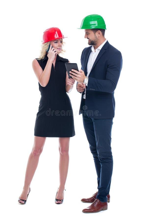 Jonge ingenieursvrouw en vrouw die in helm door mobiel communiceren royalty-vrije stock fotografie