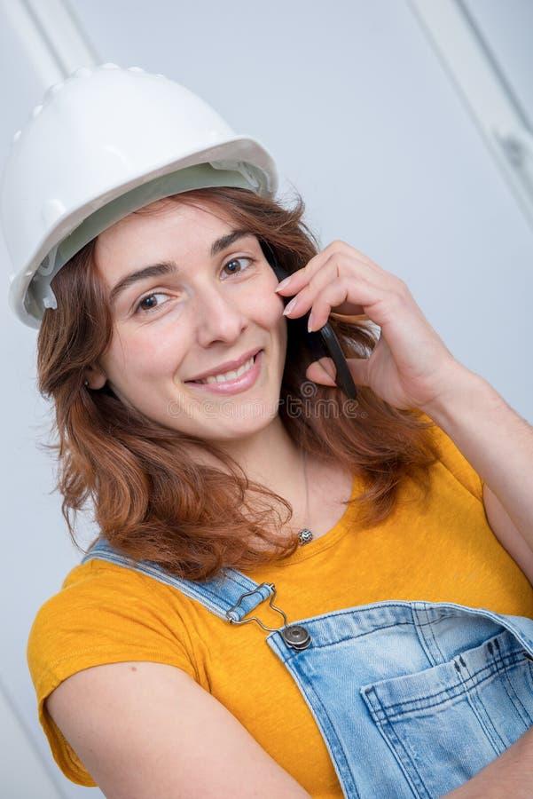 Jonge ingenieursvrouw met veiligheidshelm die op telefoon spreken royalty-vrije stock foto