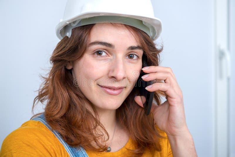 Jonge ingenieursvrouw met veiligheidshelm die op telefoon spreken stock foto's