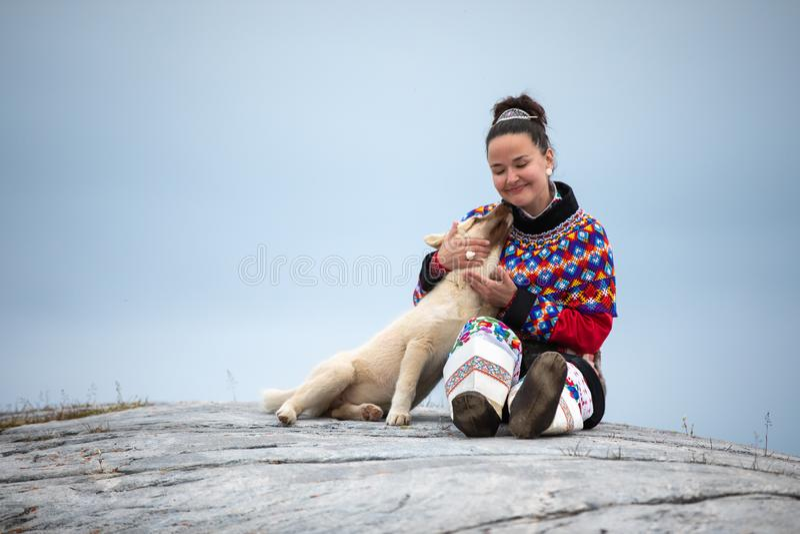 Jonge inuitvrouw in het traditionele kleding stellen voor foto's in een klein Greenlandish-dorp royalty-vrije stock foto